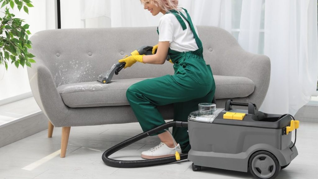 A girl in professional costume cleaning grey sofa
